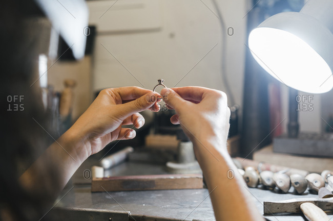 Cropped hands of female craftsperson holding ring at table in workshop
