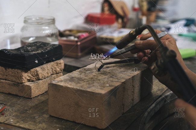 Cropped hands of female artist using blow torch on ring in workshop