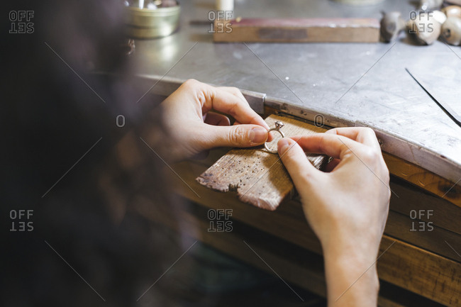 Cropped hands of female artisan holding ring on table in workshop