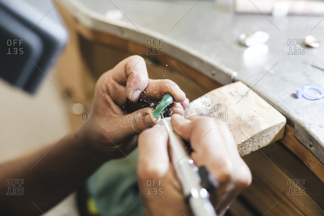 Cropped hands female artist shaping ring with equipment on table in workshop