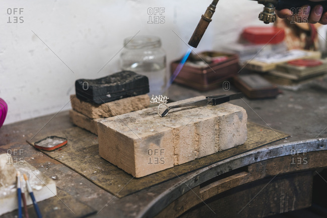 Cropped hand of female craftsperson using blow torch on ring in workshop