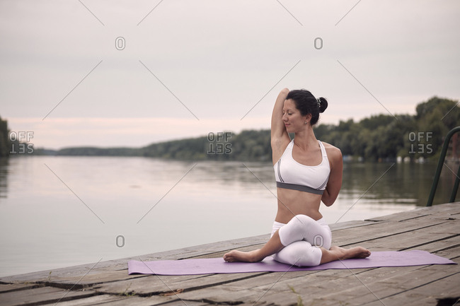Confident woman with eyes closed practicing cow face pose on pier by lake against sky during sunset