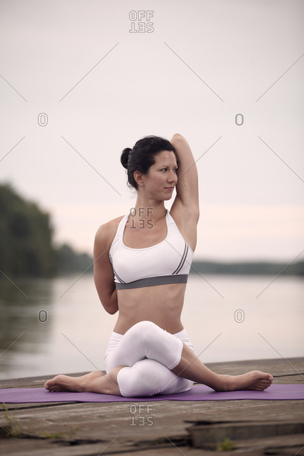 Confident woman practicing cow face pose on pier by lake against sky during sunset