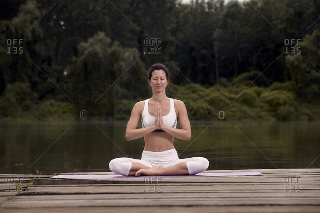 Confident woman meditating while sitting on pier by lake against trees during sunset