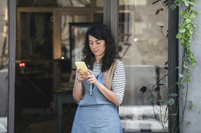 Confident female artisan using smart phone while standing by door at workshop