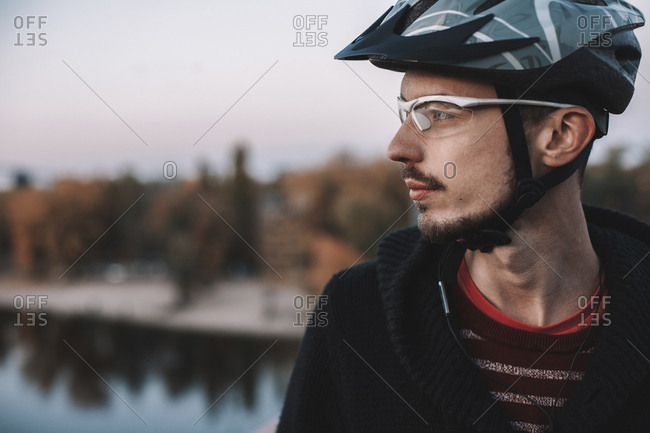 Close-up of thoughtful cyclist wearing helmet and eyewear while standing against sky during autumn
