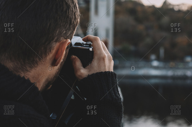 Close-up of man photographing with camera in city during sunset