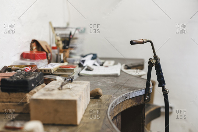 Close-up of blow torch by wooden table against wall in workshop