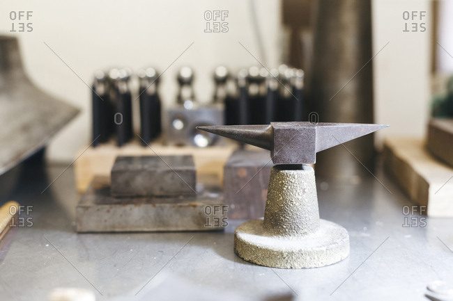 Close-up of anvil with equipment on table against wall in workshop