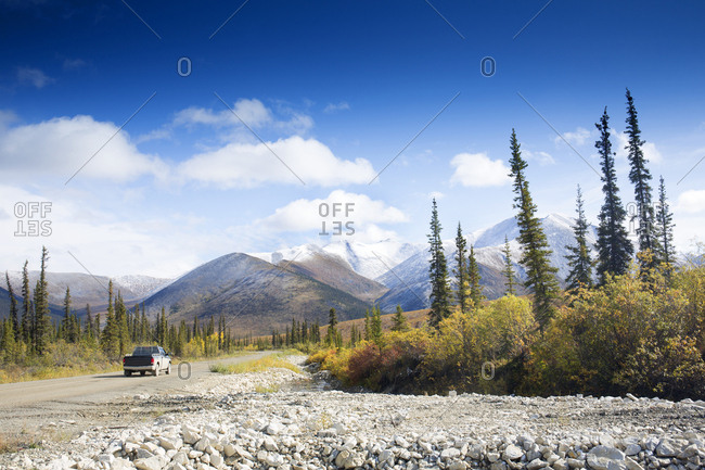 Truck on rural highway in fall, Yukon, Canada