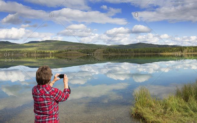 Tourist taking photograph of Hunter's lake, Yukon, Canada
