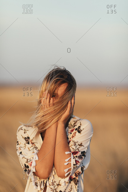 Portrait of a young woman with windblown hair and hands on face