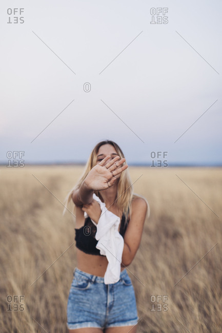 Young woman standing in a field of grass taking off her shirt
