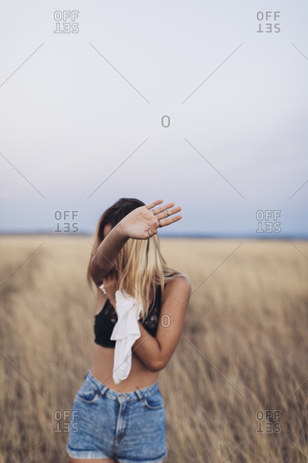 Young woman standing in a field of grass blocking view with her hand while taking off her shirt