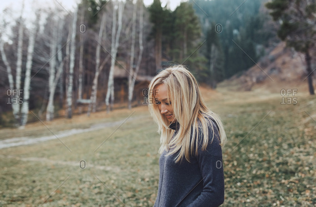 Blond woman at the mountain forest with cottage cabins