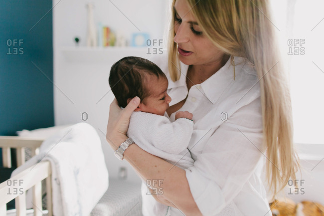 Mother holding newborn baby in nursery