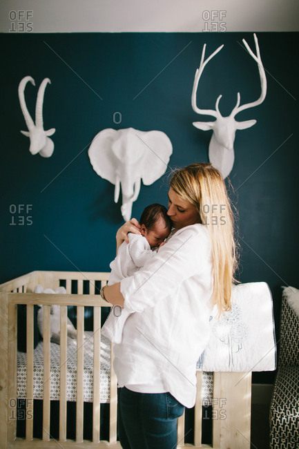 Mother kissing sleepy baby son on head