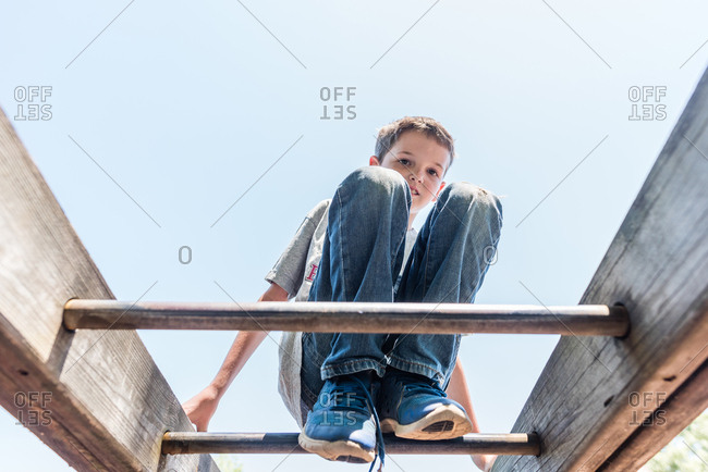 Adolescent boy climbing on the monkey bars at playground