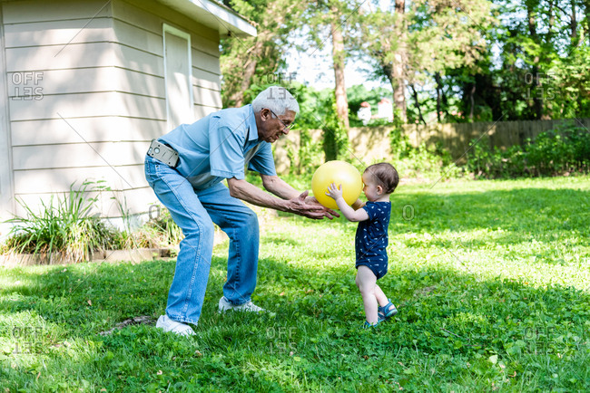 Toddler boy and grandfather playing catch with ball in the backyard