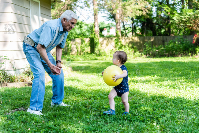 Toddler boy and grandfather playing with ball in the backyard