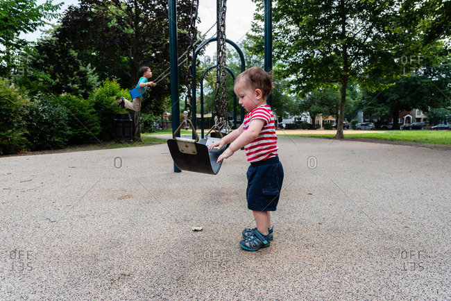 Toddler boy looking at swing on the playground