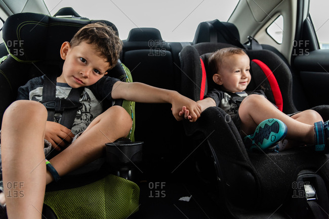 Boy holding hands with baby brother while sitting in car seats