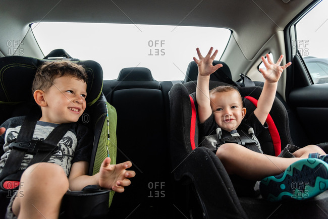 Brothers sitting in car seats on family road trip