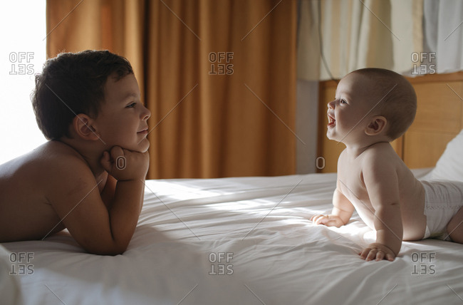 Older brother and baby brother on bed looking at each other