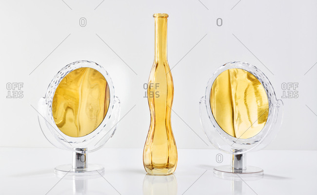 Abstract image of yellow vase and two mirrors