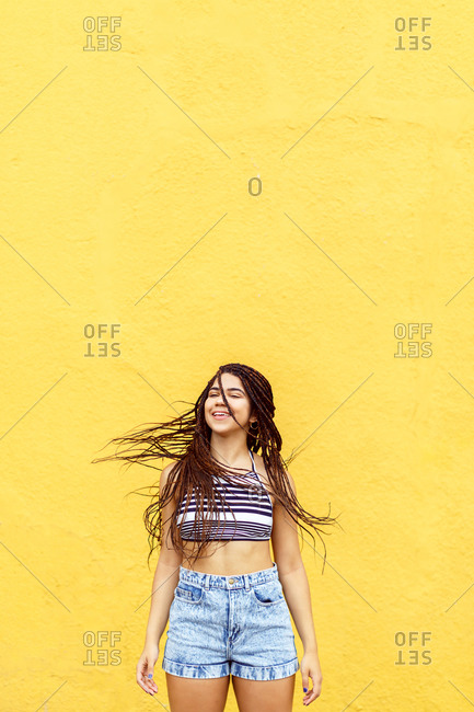 Girl swinging hair in front of yellow wall