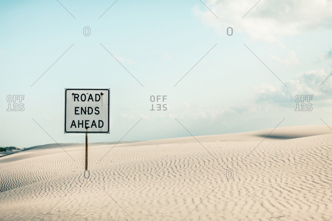 Road ends ahead - sign buried in sand