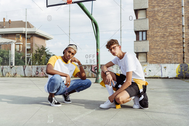Two teenage boys squatting down on the urban basket court and looking at the camera