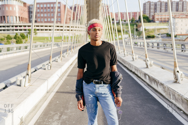 Handsome black boy with headscarf standing in the middle of the bridge looking away