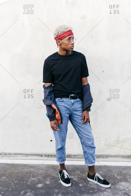 Handsome black boy standing on the street near to a wall