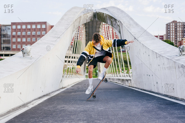 Caucasian teenager jumping with a skateboard in the middle of the bridge in the city