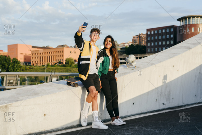 Couple of teenagers sitting on the wall and taking selfie with the phone in the street