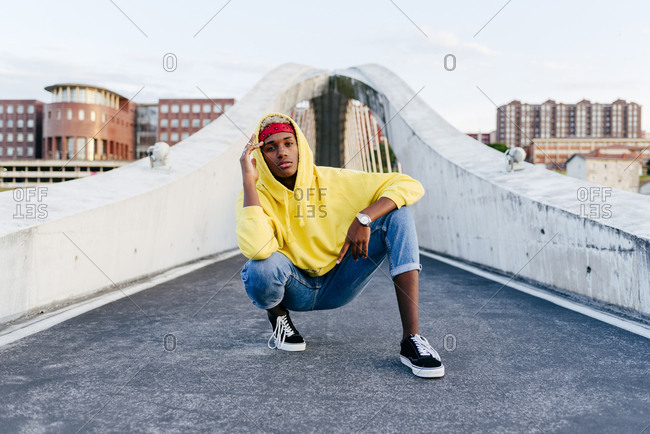 Handsome black boy with sweatshirt and hood squatting down in the street looking at the camera
