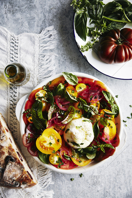 Brightly coloured salad of heirloom tomatoes in different colors, lightly picked red onion, herbs, greens, olive oil, burrata cheese. crusty olive bread.