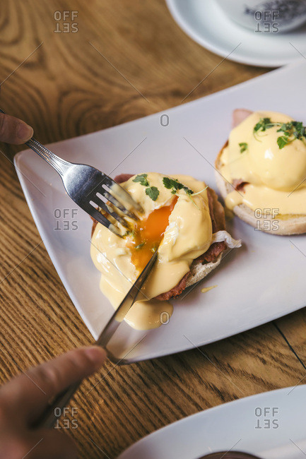 Woman eating eggs benedict served on a white plate