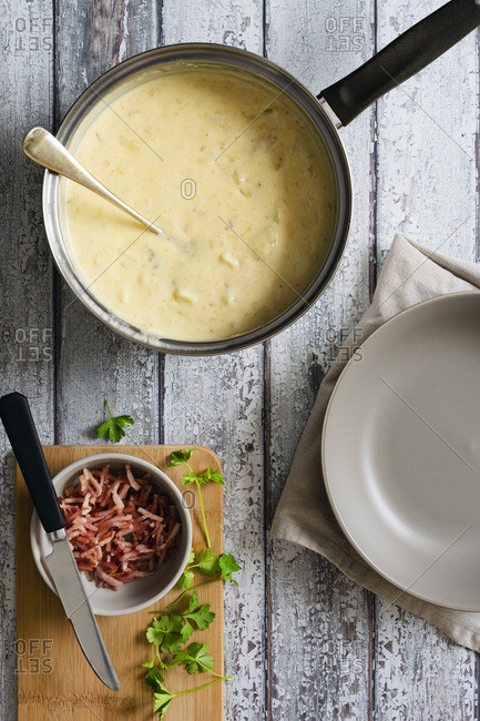 Potato and leek soup in a saucepan beside chopped parsley and bacon.