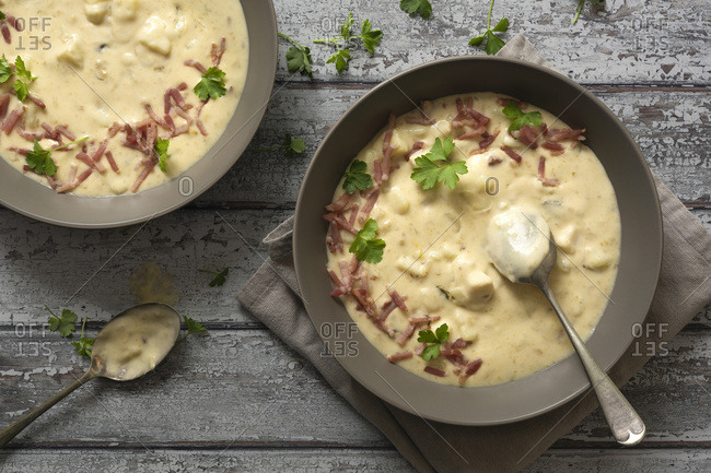 Potato and leek soup garnished with chopped parsley and bacon.