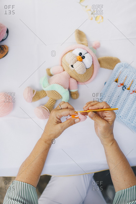 Top view of senior woman crocheting a bunny