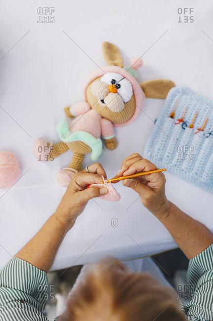 Overhead view of senior woman crocheting a bunny