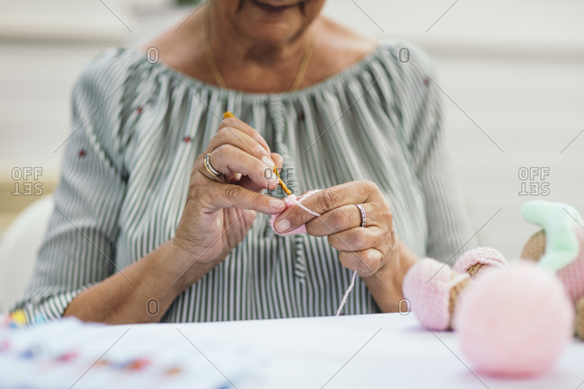 Senior woman crocheting a stuffed animal
