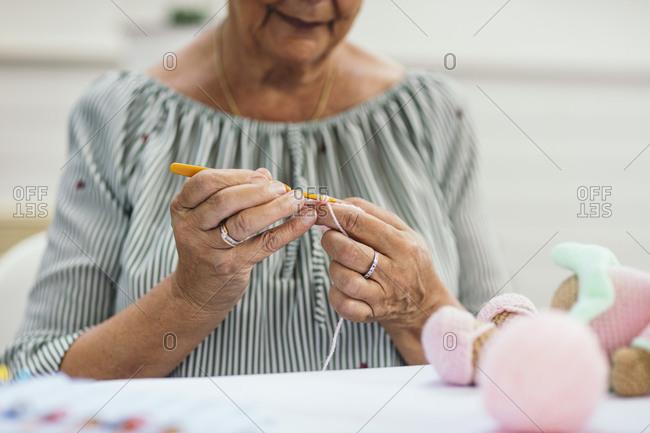 Woman crocheting a stuffed animal