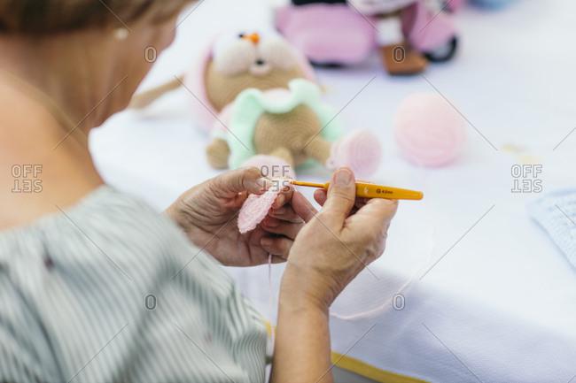 Woman crocheting a stuffed toy