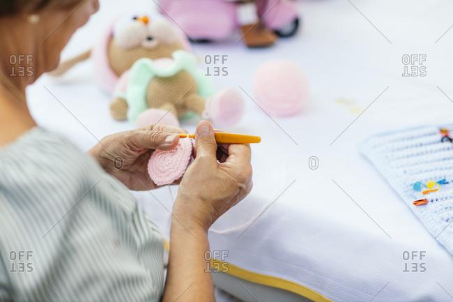 Senior woman crocheting a stuffed toy