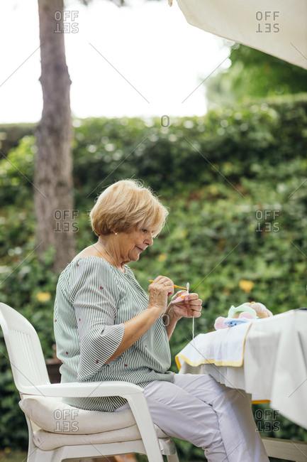 Senior woman crocheting outdoors