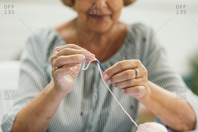 Woman using yarn and plastic needle