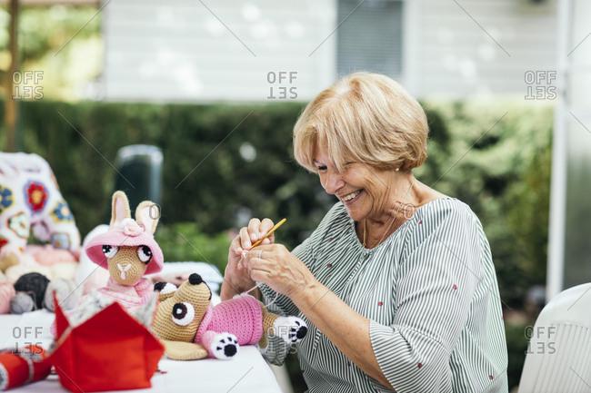 Senior woman crocheting a stuffed toy outdoors